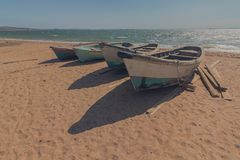 Wooden fishing boats on the sandy shore. Crimea stock images