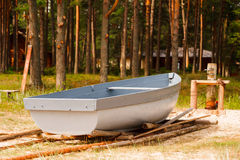 Wooden fishing rowing boat on the shore, pine trees background Royalty Free Stock Photography