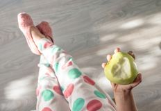 Wooden floor baby legs in pajamas polka dots and knitted slippers pastel tones hand holding an apple bite in the shape of a heart stock photo