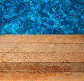 Wooden floor beside blue pool water Royalty Free Stock Images