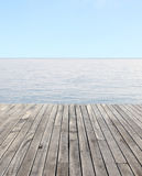 Wooden floor and blue sea with waves and clear blue sky Stock Image