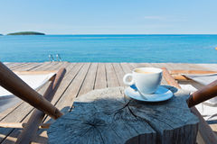 Wooden floor with chaise-longues and coffee Royalty Free Stock Photography