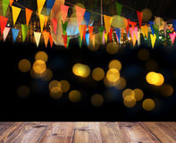 Wooden floor and colorful flags over bokeh for night party decor. Night party decoration background, wooden floor and colorful flags over bokeh, vintage filter Stock Image