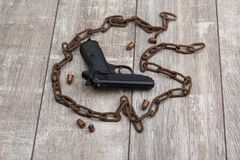 On a floor, a few ammunition, a pistol and rusty chain. Stock Photography