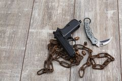 The layout of a black pistol, several scattered cartridges, a folding knife and an old rusty chain. Stock Photos