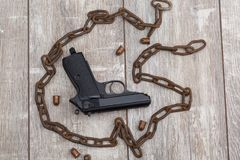 The layout of the rusty chain is lined in the form of a circle inside which there is a pistol and a ammunition. On the wooden floor the layout of the old rusty Stock Images