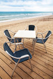 Wooden floor and metal armchairs on the sandy beach Stock Photo