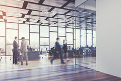 Wooden floor open space office, people. Open space office interior with a wooden floor, a glass wall, a rectangular ceiling pattern and panoramic windows royalty free stock image