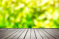 Wooden floor perspective and green forest. Blured with bokeh and ray of sun light Royalty Free Stock Photos