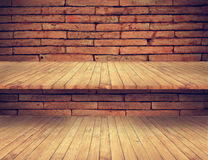Wooden floor and shelves on old brick wall texture Royalty Free Stock Photos