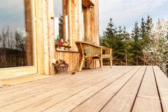 Wooden floor, Wooden terrace at an ecological house. Wicker chairs on a wooden terrace by the forest.  stock photos