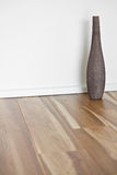 Wooden floor with white wall and vase Stock Images