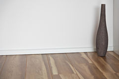 Wooden floor with white wall and vase Royalty Free Stock Photo