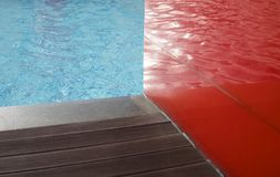 Wooden flooring beside the pool. Wooden flooring bee the pool with water surface reflection on the red glass wall Stock Photography