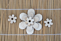 Wooden flower decoration on a reed background Stock Images