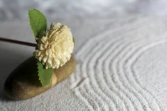Wooden flower and stone stock photography
