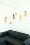 Wooden flowerpots on the wall. Wooden flowerpots with plants inside in the room with white wall and black leather sofa royalty free stock photos