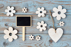 Wooden flowers, heart, black chalk board on  a blue grey knotted old wooden background with empty space layout Royalty Free Stock Image