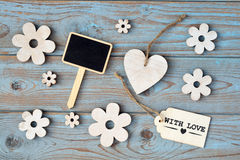 Wooden flowers, heart, black chalk board and with love label on  a blue grey knotted old wooden background with empty space layout Stock Photo