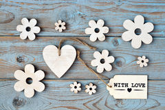Wooden flowers, heart, black chalk board and with love label on  a blue grey knotted old wooden background with empty space layout Royalty Free Stock Photo