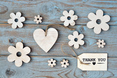 Wooden flowers, heart, black chalk board and thank you label on a blue grey knotted old wooden background with empty space layout