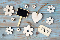 Wooden flowers, heart, black chalk board and for you label on  a blue grey knotted old wooden background with empty space layout Royalty Free Stock Photography