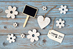 Wooden flowers and heart on a old wooden background with thank you  label and  and black chalk boardempty space layout Royalty Free Stock Image