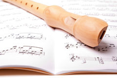 Wooden flute. On sheet music. Close up Stock Image
