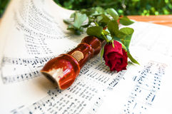 Wooden flute and a red rose on music scores Stock Photo