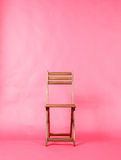 Wooden folding chair on red background Royalty Free Stock Images
