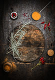 Wooden food background with old dark chopping cutting board, herbs and spices Royalty Free Stock Image