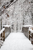 Wooden foot bridge covered in snow in a winter forest Stock Images