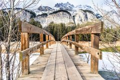 Wooden foot bridge leading over glacial stream to inspiring wint. Er mountains landscape. Snow capped mountain and forest in distance Stock Photo