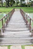 Wooden foot bridge in the park with trees. Wooden foot bridge crossing the pond in the park with trees royalty free stock photos