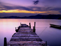 Wooden Foot Bridge and small boat at Sunset Royalty Free Stock Photos