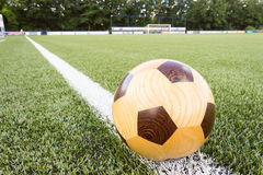 Wooden football on sideline Royalty Free Stock Photo