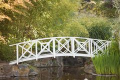 Wooden Footbridge. Small white wooden footbridge in a garden over a pond Royalty Free Stock Photos