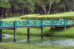 A wooden footbridge across a brook in the park. Royalty Free Stock Photos