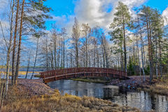 Wooden footbridge. Across the channel between lakes at autumn forest in Finland Stock Image