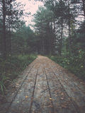 Wooden footbridge in the bog. Vintage. Stock Images