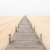 Wooden footbridge on a foggy beach background. Royalty Free Stock Images