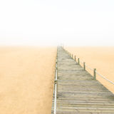Wooden footbridge on a foggy sand beach background. Portugal. Royalty Free Stock Photo