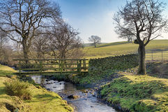 Wooden footbridge and ford crossing a small stream Stock Image
