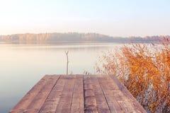 Wooden footbridge on the lake at sunrise on a foggy morning.  royalty free stock photo