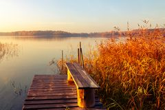 Wooden footbridge on the lake at sunrise on a foggy morning.  stock photography