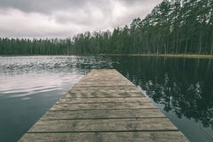 Wooden footbridge in the lake - vintage green look. Wooden footbridge in the lakein the countryside surrounded by forest - vintage green look stock image