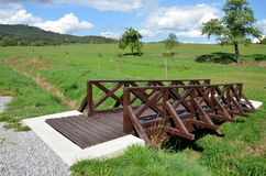 Wooden footbridge over drain on the meadow Royalty Free Stock Images