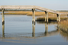 Wooden footbridge over North Carolina swamp. This footbridge over marsh swamp in North Carolina reflect in the water on a sunny day Royalty Free Stock Photo