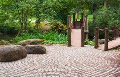 Wooden footbridge over river in the garden. Royalty Free Stock Image