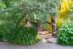 Wooden footbridge over river in the garden. Stock Images